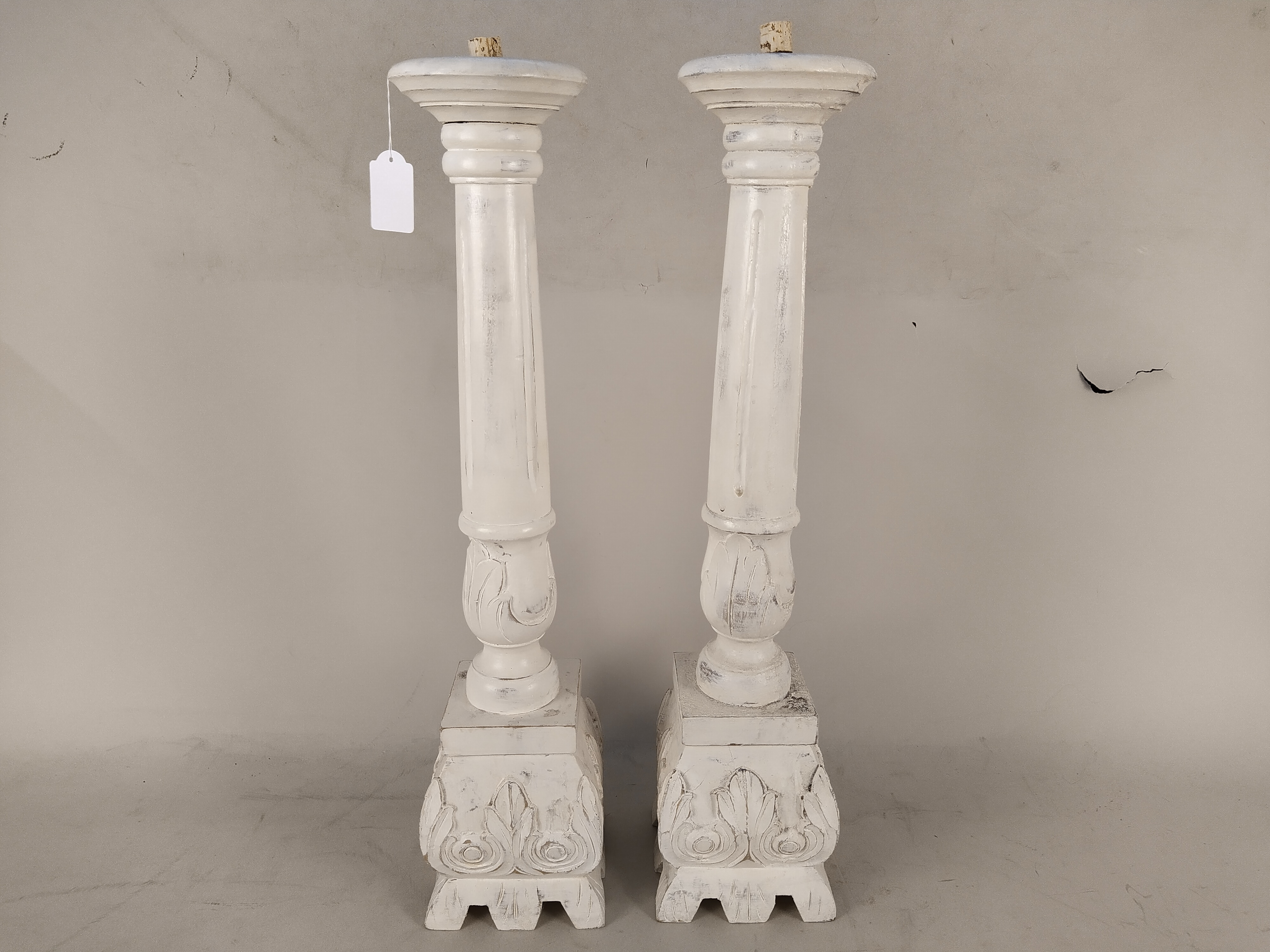 A pair of large white finish and distressed wood candle stands,