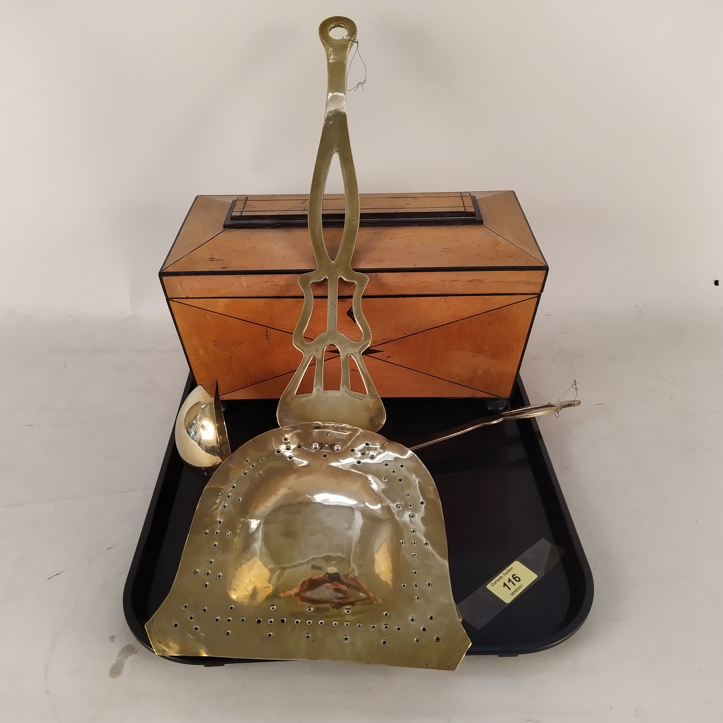 An antique satinwood tea caddy with void interior plus a Victorian brass chestnut roaster and ladle