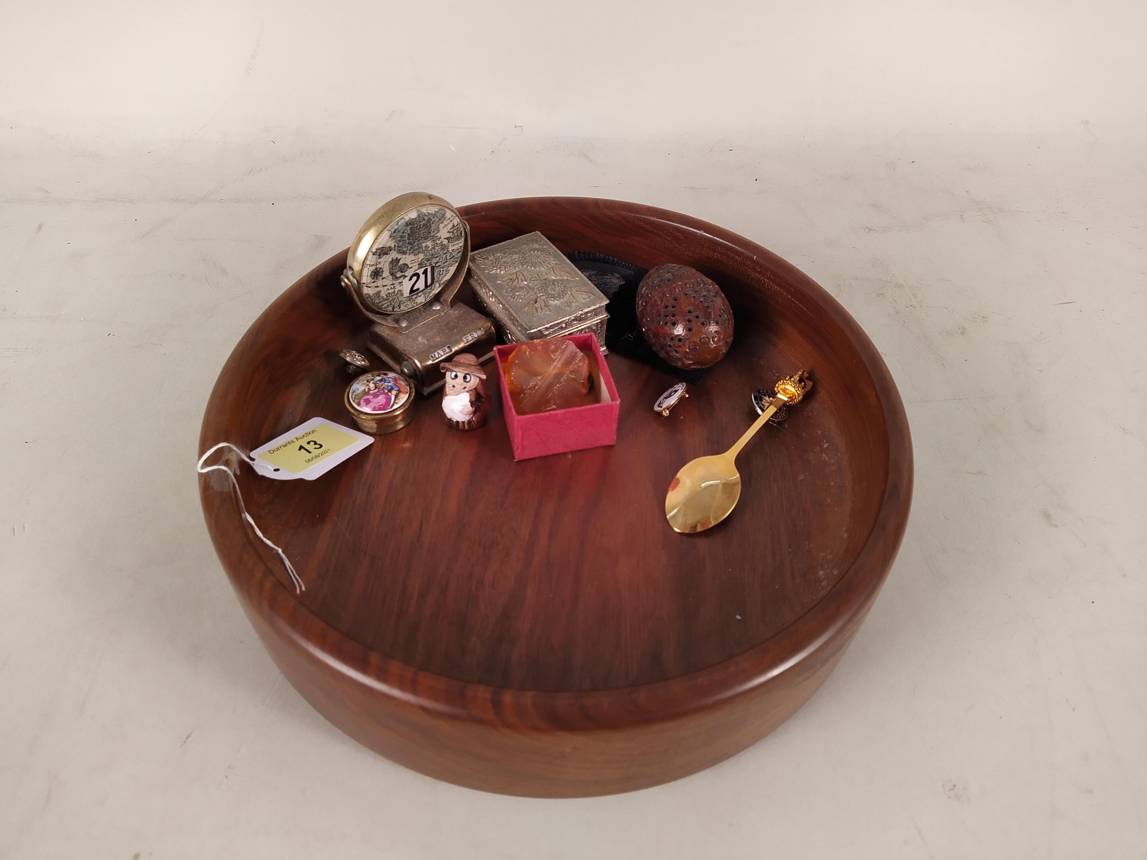 A wooden fruit bowl and contents including a desk calendar,