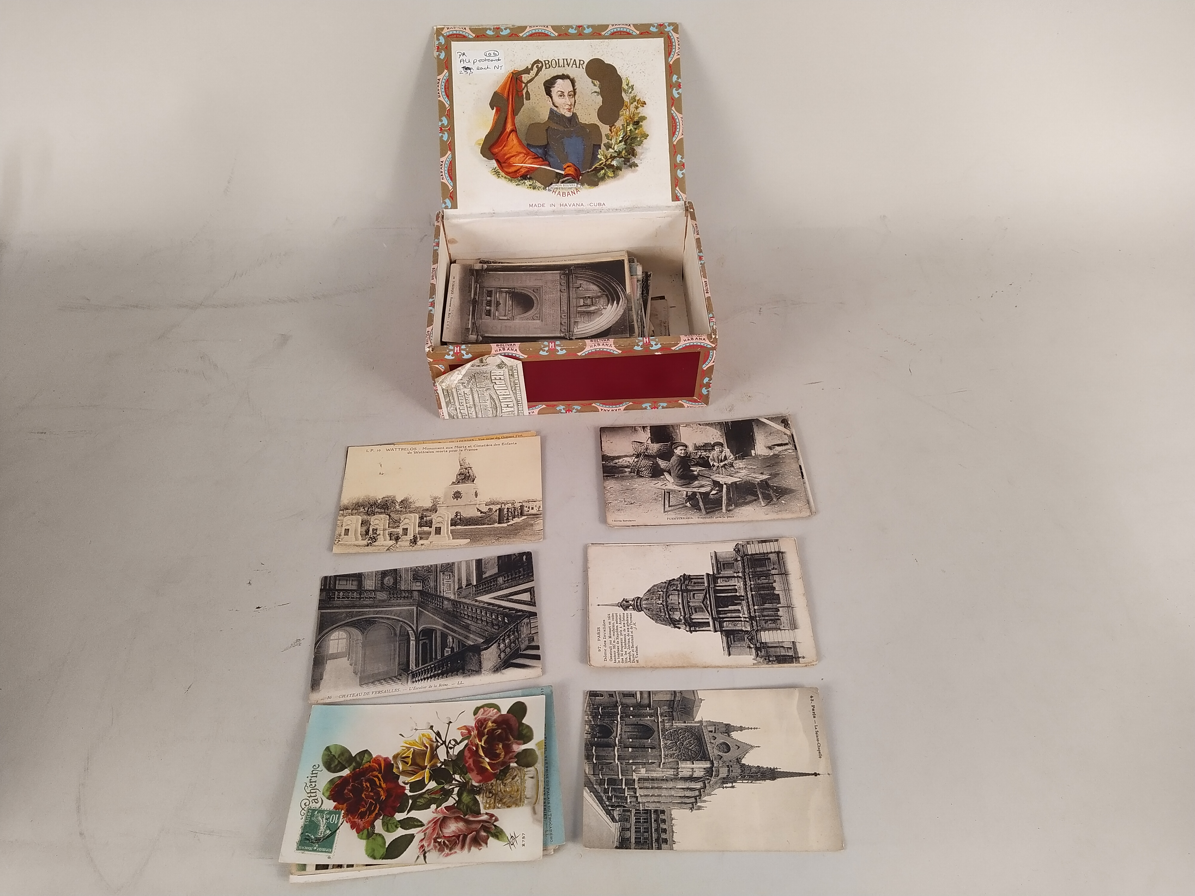 A selection of early 20th Century postcards in old cigar box plus an antique chestnut roaster and