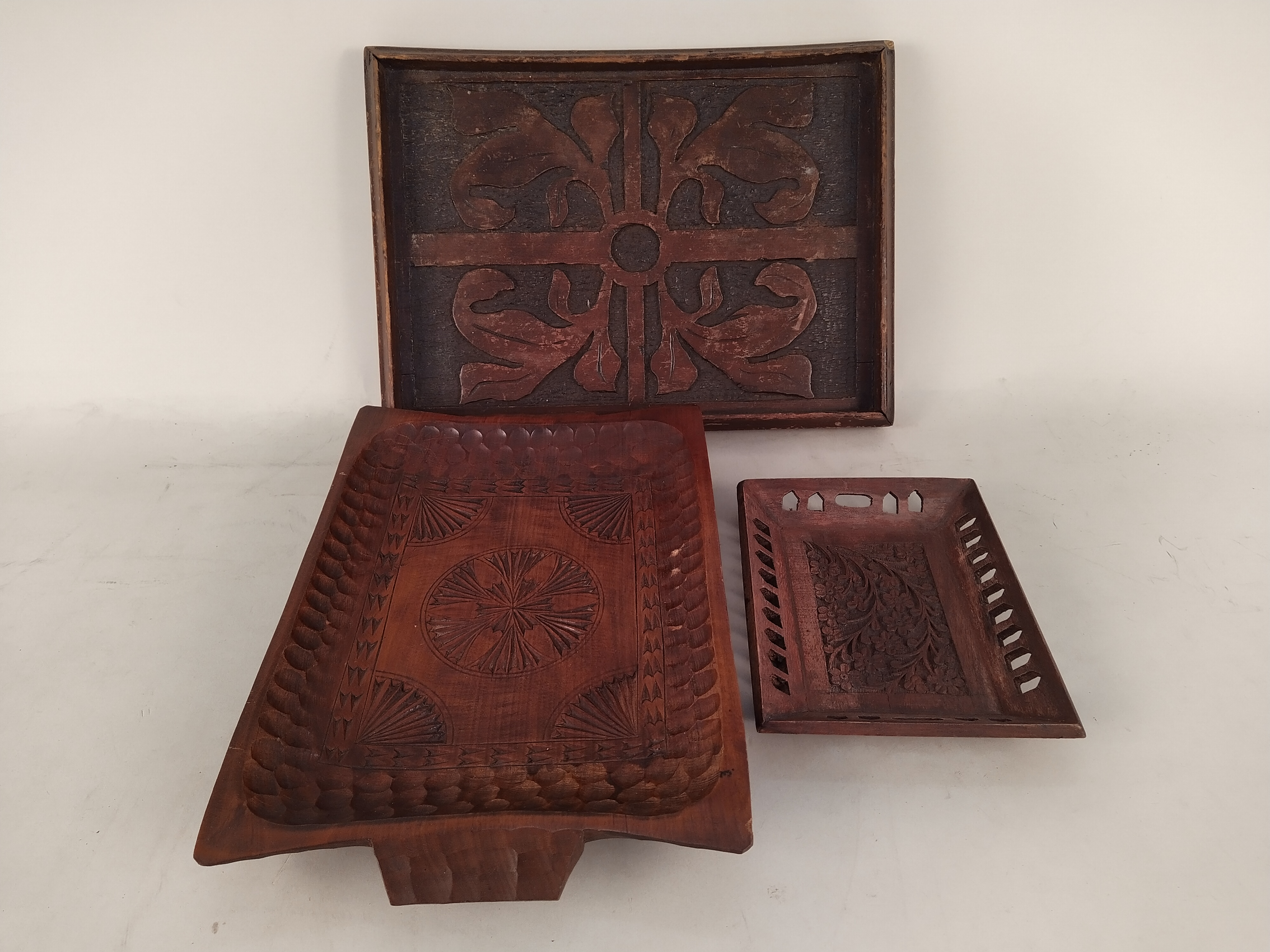 A selection of vintage carved wooden trays including a Trinidad nut tray