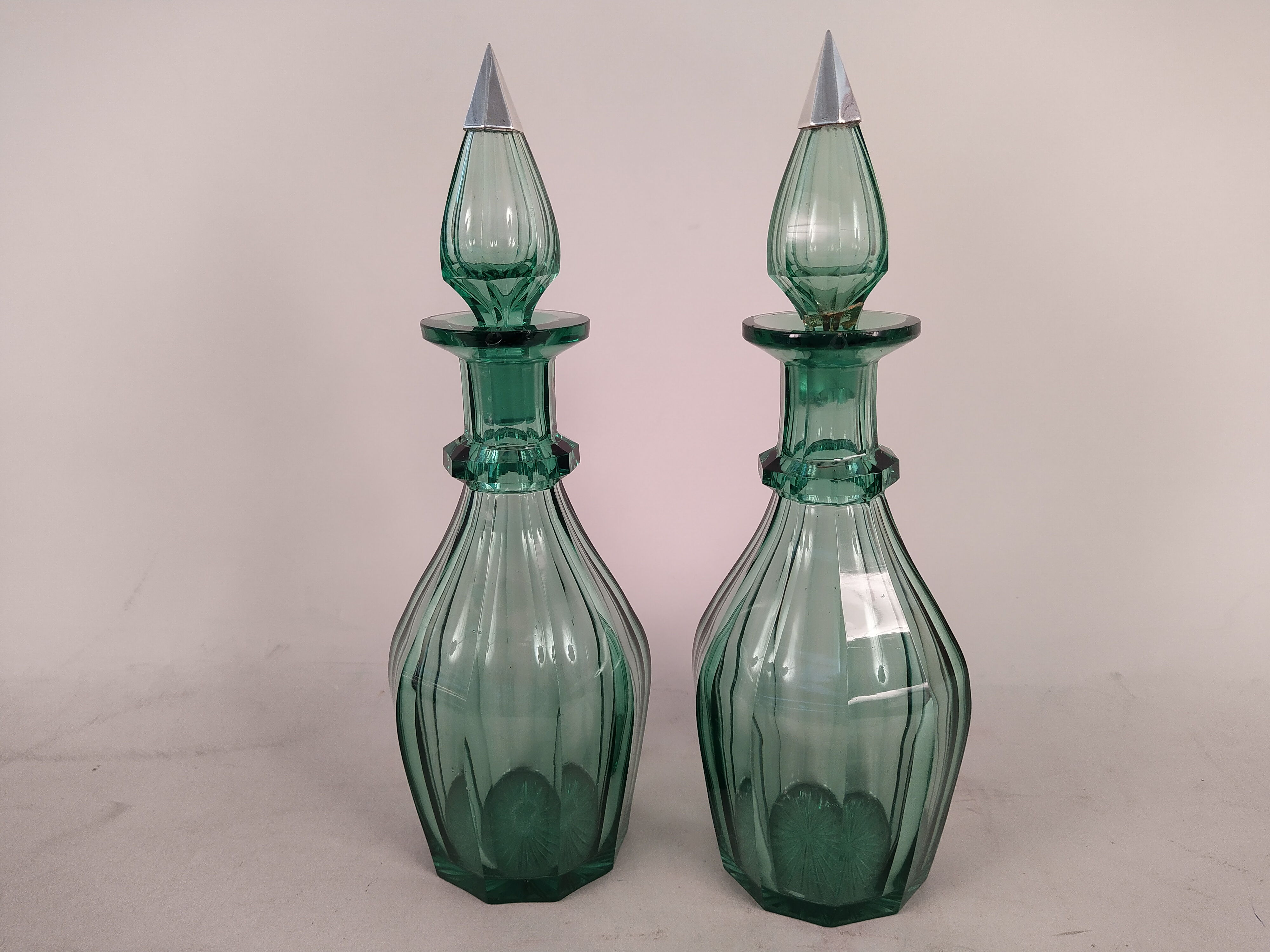 A pair of hand blown and cut green decanters (some chips to neck and an old repair to stoppers)