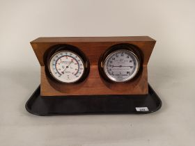 A ships style thermometer plus a humidity indicator in a hardwood frame of West German manufacture