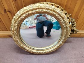 Two round and one oval gilt framed mirrors,