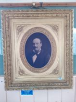 A late 19th Century French portrait photo of a gentleman in an oval gilt mount within a heavily