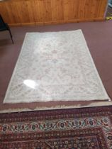 A wool rug with pale floral patterns against a beige ground,