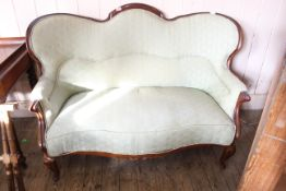 A Victorian mahogany framed sofa with carved arms on cabriole legs