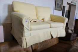 An upholstered two seater sofa with yellow loose covers