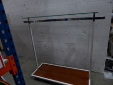 * metal rail with wood effect bottom shelf and glass over shelf on castors. Adjustable height. 1600w