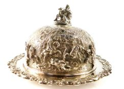 A George IV silver muffin dish and cover, the domed cover with a finial of a seated man with dog,