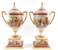 A pair of Vienna style late 19thC porcelain vases and covers, mounted on plinths, of twin handled