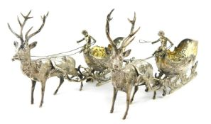 A pair of Continental silver bonbon dishes, modelled as reindeer pulling sleighs, surmounted with
