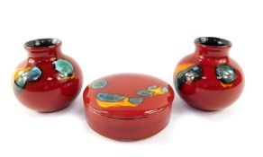 A group of Poole pottery decorated in the Volcano pattern, comprising a pair of vases, 10cm high,