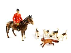 A Beswick pottery figure of a huntsman on a brown gloss horse, together with four hounds and a