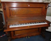 A Victorian walnut cased upright piano, makers label lacking, with carved pilasters, memorial plaque