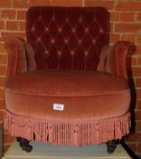 A Victorian button back armchair, upholstered in pink draylon, raised on turned feet and castors.