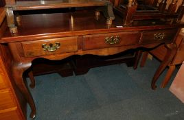 A reproduction mahogany side table, with three drawers raised on cabriole legs, 70cm high, 122cm