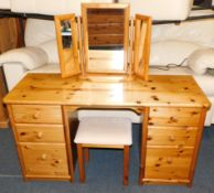A pine dressing table, of six drawers, 75cm high, 138cm wide, 49cm deep., with tryptic mirror and