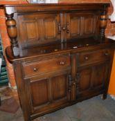 A dark oak Ercol court cupboard, with carved panel doors, label to right door, 124cm high, 123cm