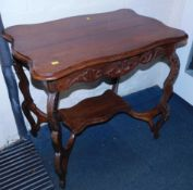 An early 20thC walnut two tier occasional table, with carved apron and legs, 71cm high, 77cm wide,