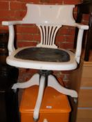 An early 20thC wooden framed desk chair, painted white, with upholstered seat.