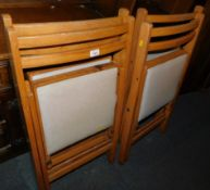 A set of four mid 20thC beech framed folding chairs, with cream vinyl seats.