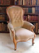 A Victorian mahogany show frame armchair, upholstered in button beige fabric, on cabriole legs