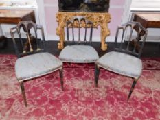 A set of three George III painted side chairs, each decorated in gilt with swags, patera, etc, on