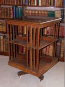 A Edwardian mahogany revolving bookcase, with slatted supports on X shaped base with ceramic