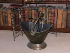 A late 19th/early 20thC brass and copper coal helmet, with swing handle, fire iron and a spark