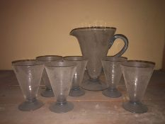 A 1930's glass lemonade set, comprising six tapered crazed conical glasses with blue feet and a