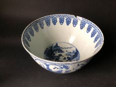 An 18thC Chinese punch bowl, handpainted with blue on white having a central reservoir of trees,