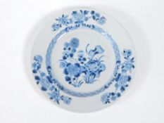 A 18thC Chinese blue and white plate, decorated with a floral landscape, 23cm diameter.