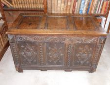 A late 17thC oak coffer, with a triple plank hinged top, the front carved with lozenges, scrolls and