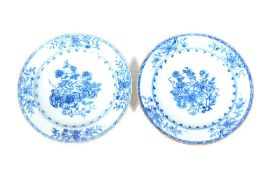 A pair of mid 18thC Chinese blue and white plates, decorated with flowers and foliage, 23cm