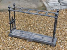A Victorian cast iron umbrella stand, with five divisions, on spiral end supports, headed by