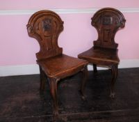 A pair Victorian oak hall chairs, the shield shaped back with carved Pegasus crest, the solid