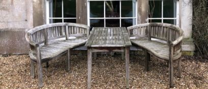 A hardwood garden suite, comprising two curved serpentine benches and lath top rectangular table