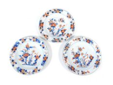 Three 18thC Chinese plates, polychrome decorated with floral landscape patterns, 23cm diameter. (3)