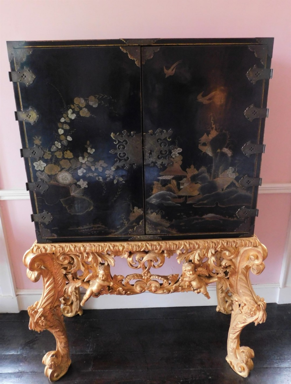 A late 17th/early 18thC Japanned cabinet, decorated in gilt and silver with flowers, buildings, etc.