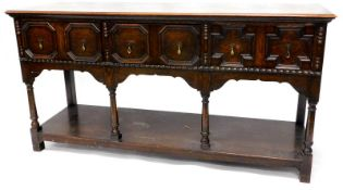 An early 20thC oak dresser base, the top with a moulded edge above three panelled drawers, on turned