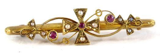 An early 20thC gold bar brooch, inset with seed pearls and rubies, stamped to the reverse 15ct. (2.