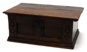 A late 17th/early 18thC oak Bible box, the panelled front carved with bell flowers, on a plinth