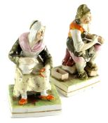 A pair of 19thC Staffordshire figures of cobblers, each polychrome decorated on square gilt line
