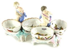 A pair of late 19th/early 20thC Sitzendorf style figural salts, each painted with birds, insects,