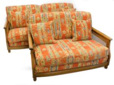 An Ercol elm and caned three seater sofa, and a matching two seat sofa, with geometric multicoloured