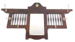 A late Victorian oak framed wall mounted coat rack, with a central rectangular bevelled glass