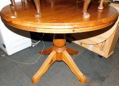 A circular pine kitchen table, 78cm high, 107cm diameter.