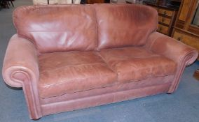 A brown leather two seater sofa, raised on bun feet, 199cm wide.