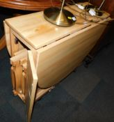 A beech drop leaf kitchen table, 75cm high, 31cm wide, 141cm extended, 86cm deep, enclosing four
